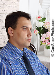 Beautiful young serious man sits near table with flowers in white room