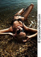 Beautiful young sexy blonde wearing sunglasses, laying in...