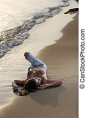Beautiful young sexy fashion model in jeans by the sea at...