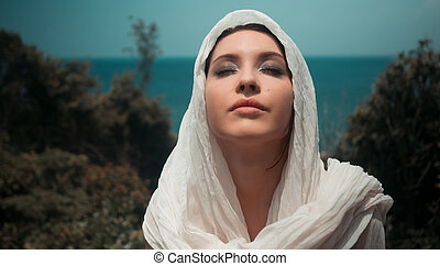 Beautiful young sexy girl with bright make-up in a creamy headscarf