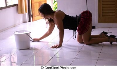 Beautiful young sexy maid on her knees cleans tiled floor, concept cleaning.