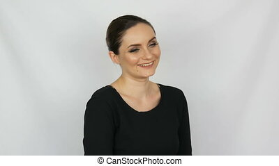 Beautiful young sexy woman in black dress approvingly with love gently and smilingly looking on a white background in the studio.