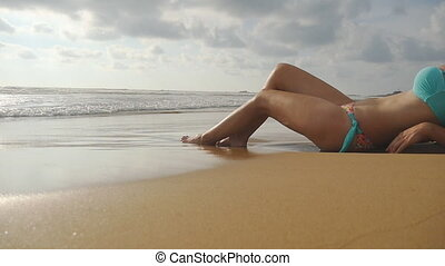 Beautiful young sexy woman lying on golden sand on sea beach and relaxing during summer vacation travel. Ocean waves washing over tanned female feet. Slow motion