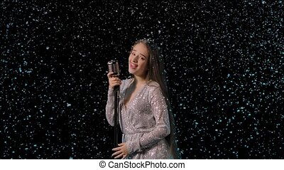Beautiful young sexy woman with long hair in an evening dress sings into a vintage microphone. The soloist smiles and elegantly moves against the background of falling snow. Close up. Slow motion.