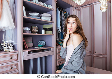 Beautiful young shocked woman don't know what to wear...