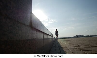 Beautiful young slender girl rides a skateboard along the...