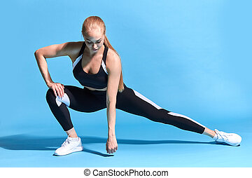 Beautiful young slim flexible girl stretching her hamstrings.