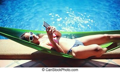 Beautiful young slim woman in bikini laying down in hammock...