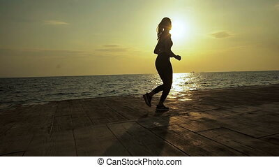 Beautiful young slim woman running in the evening near the sea.
