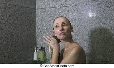 Beautiful Young Slim Woman Taking a Shower and Washing Hair...