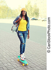 Beautiful young smiling african woman riding on skateboard in city