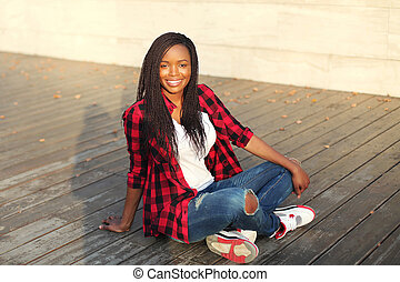 Beautiful young smiling african woman sitting in city evening