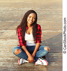Beautiful young smiling african woman sitting resting in city