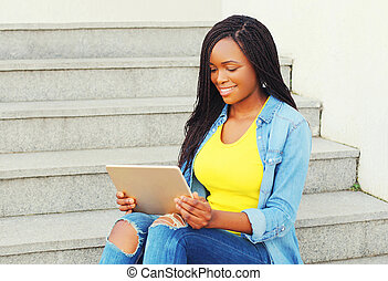 Beautiful young smiling african woman using tablet pc computer sitting in the city
