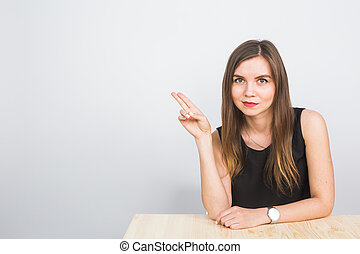beautiful young smiling businesswoman pointing at copy space