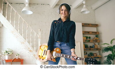 Beautiful young smiling girl in headphones posing with electric guitar at home studio indoors