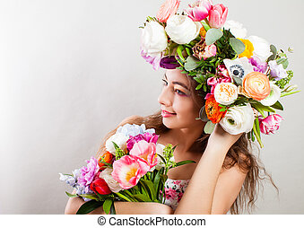 Beautiful young smiling model with bright flowers on her head