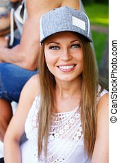 Beautiful young smiling sporty girl sitting on a bench in a park