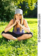 Beautiful young smiling sporty girl sitting on a grass in a park