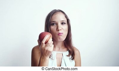 Beautiful young smiling woman eating red apple fruit. slow motion. Isolated on White Background. 3840x2160