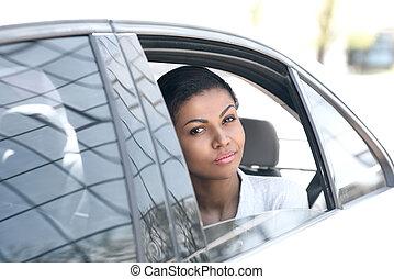 Beautiful young smiling woman looking through car window