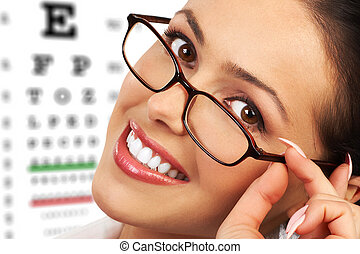 Beautiful young smiling woman with eyeglasses and eyechart