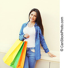 Beautiful young smiling woman with shopping colorful bags in jeans clothes