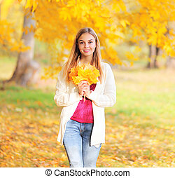 Beautiful young smiling woman with yellow maple leafs in autumn park