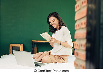 Beautiful young smiling woman working on laptop while sitting on bed at home