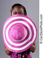 Beautiful young South African woman in bright colors holding a hat.