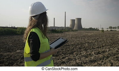 Beautiful young specialist female engineer checking and calculating with electronic device tablet pc environmental pollution data near petroleum refinery