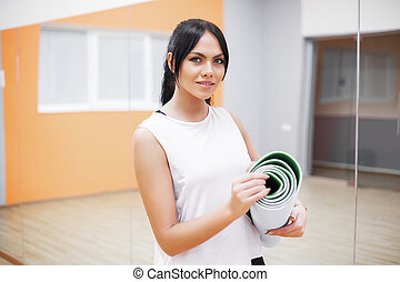 Beautiful young sport fitness woman make exercises holding fitness rug