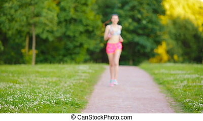 Beautiful young sport girl engaging in gymnastics outdoors. Runner - woman running outdoors training for marathon run