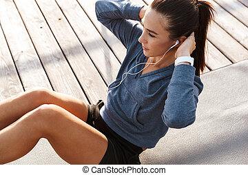 Beautiful young sports fitness woman make sport exercises at the beach outdoors listening music with earphones.