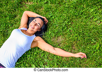 Beautiful young sporty girl in the grass