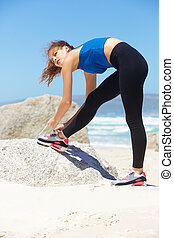 Beautiful young sporty woman tying shoelace