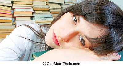 Beautiful young student girl almost asleep on her books