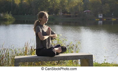 Beautiful young student girl doing yoga outdoor in nature and meditating in lotus position one day before her exams in slow motion