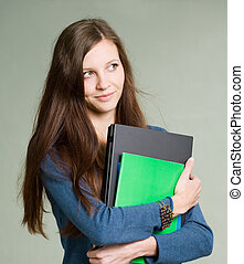 Beautiful young student girl holding laptop.