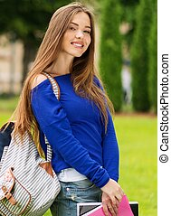 Beautiful young student girl in a city park on summer day