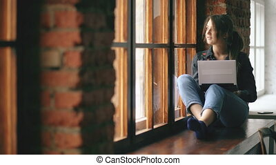 beautiful young student girl with laptop sitting on a windowsill in university classroom indoors