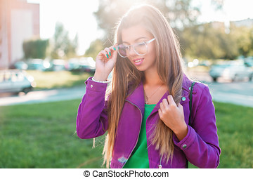 Beautiful young stylish woman in sunglasses walking in the park on a sunny summer day.