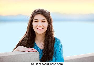 Beautiful young teen girl enjoying outdoors by lake at sunset