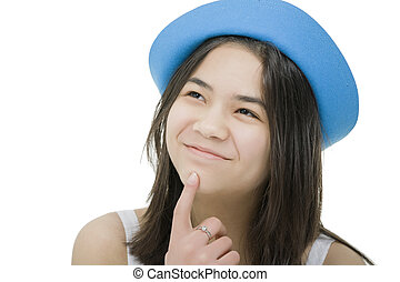 Beautiful young teen girl in blue hat, looking up with thoughtful expression, as if just had an idea.