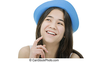 Beautiful young teen girl in blue hat, looking up with thoughtful expression, as if she has a fun idea or thought. Isolated on white