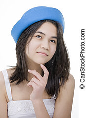 Beautiful young teen girl in blue hat, looking up with thoughtful expression, finger touching chin. Isolated on white