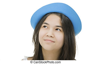 Beautiful young teen girl in blue hat, looking up with thoughtful expression.Isolated on white