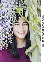 Beautiful young teen girl standing under wisteria vines