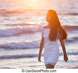 Beautiful young teenager with a white dress on the beach at...