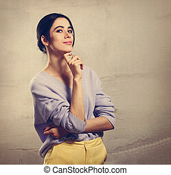 Beautiful young thinking woman looking up with hand under the face in violet sweater and yellow pants on grey studio background. Portrait of smiling natural european girl.
